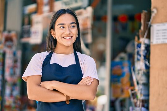Young latin shopkeeper girl with arms crossed smiling happy at the press shop