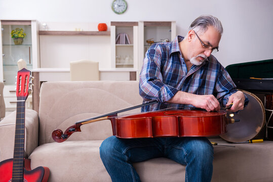 Senior male repairman repairing musical instruments at home