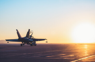 Jet fighter on an aircraft carrier deck against beautiful sunset sky . Elements of this image furnished by NASA