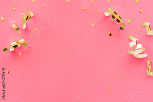 gold color of rolling ribbon and confetti on pink background with copy space for valentine and mother's day and women's day celebration design concept