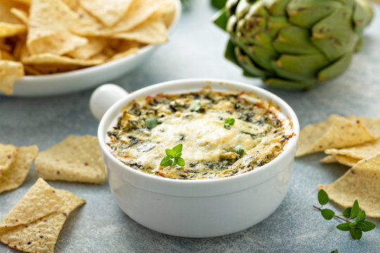 Artichoke spinach dip in a baking dish served with chips
