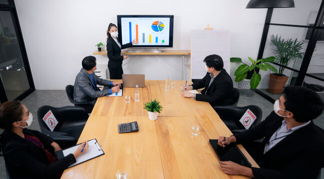 Young businessman talking to his coworkers while analyzing charts during a meeting