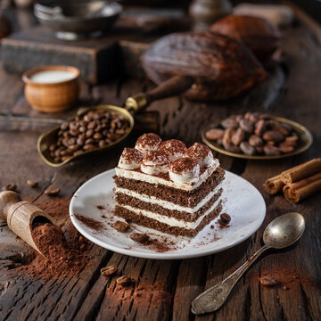 Slice of chocolate cake with tiramisu cream and cocoa powder on wooden table.