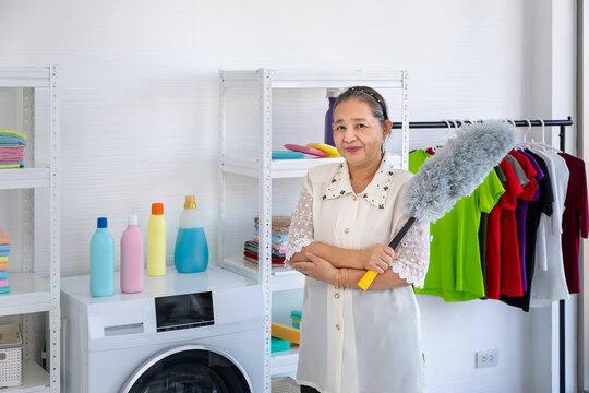 Asian senior elder woman holding feather duster laundry room with proud, looking at camera, spring cleaning concept