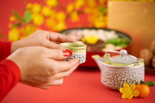 Hands of woman drinking cup of green tea with sweet driend fruits at Chinese New Year celebration