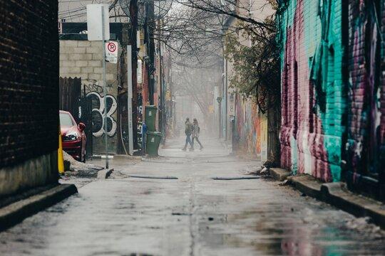 couple walking through graffiti alley