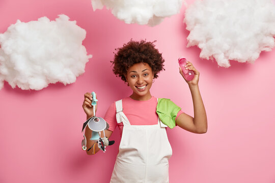 Beautiful cheerful dark skinned woman expects baby has big tummy dressed in white sarafan holds mobile and feeding bottle prepares to become mother isolated over pink background. Happy expectation