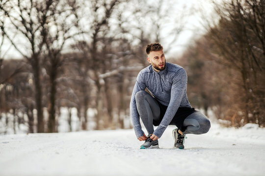 Sportsman crouching on trail in nature and tying shoelace at snowy winter day. Healthy lifestyle, sportswear, snowy weather