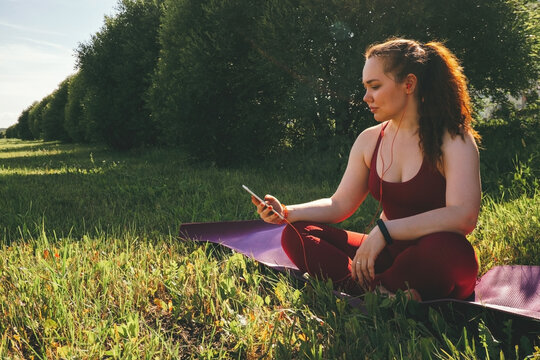 young beautiful woman in red leggings and a top practicing yoga in a city park