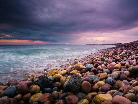 Playa de rocas al atardecer con cielo nuboso amenazando tormenta