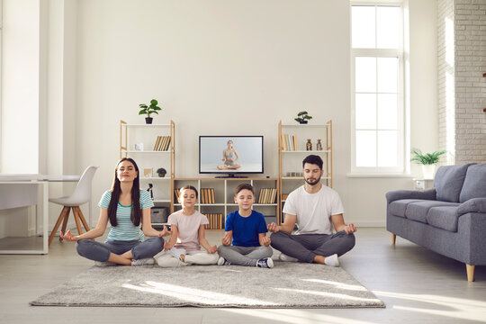 Lockdown pastime good for physical and mental health. Calm parents and children doing yoga at home. Happy family with kids sitting cross-legged on warm floor rug and practicing meditation together