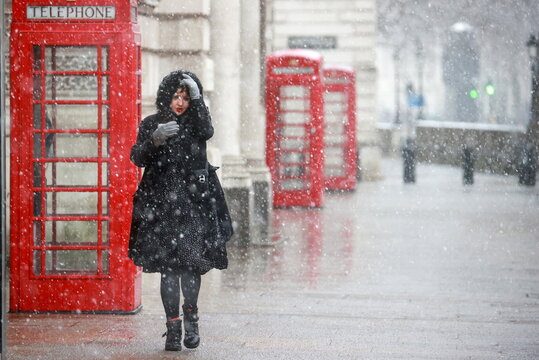 A person walks past a phone booth during snowfall in London