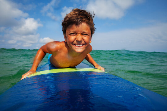 Close portrait of the boy on the surfing board smiling to the camera with funny head