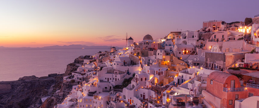 Beautiful view of fabulous caldera view, picturesque village of Oia with traditional white houses under sunset. Amazing travel vacation landscape. Stunning sunset night view Santorini island, Greece