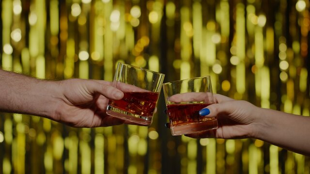 Raising toast with glasses of brandy or rum. Two hands with glasses of cognac whiskey with ice cubes making cheers on gold background. Celebration of business success, Christmas, anniversary, birthday