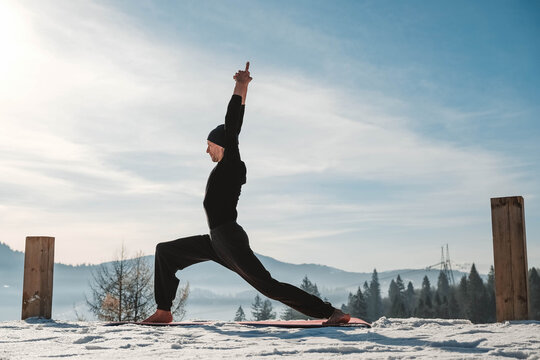 Caucasian senior man doing yoga exercises in front of amazing sunset on the winter mountains. Copy, empty space for text