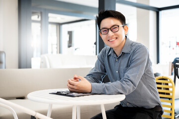 Happy young man sitting in modern office and  looking at the camera with smile