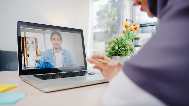 Asia muslim businesswoman using laptop talk to colleague about plan by video call brainstorm online meeting while remotely work from home at living room. Social distancing, quarantine for corona virus