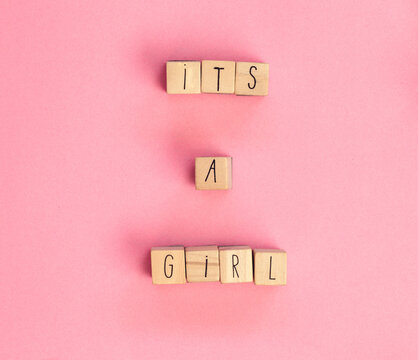 Its a Girl text written with wooden cubes on pastel white background top view, Baby announcement. Flat lay,text space. Greeting card, shower, baby concept bright colorful design