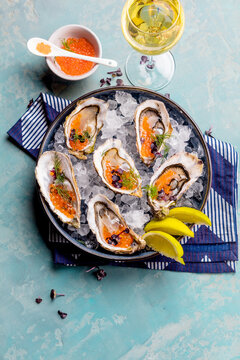 Oysters platter with lemon caviar and ice served on a Blue marine table.