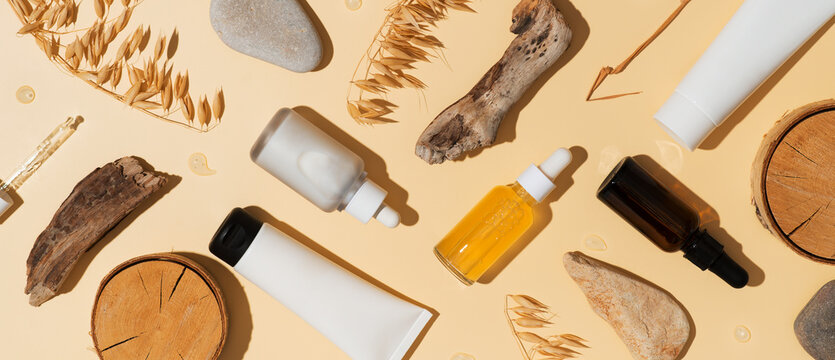 Natural cosmetic concept with serum and cream tube and bottles with natural materials