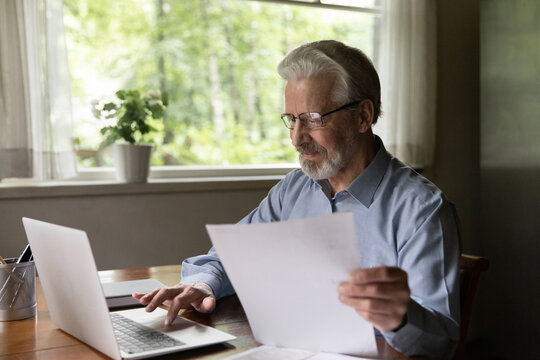 Close up satisfied mature man wearing glasses reading good news in document, holding paper sheet, using laptop, browsing online banking service, checking loan agreement, calculating bills at home