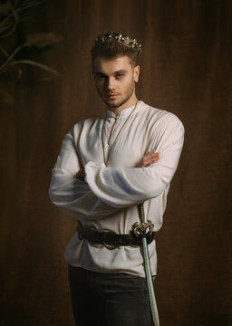 Portrait of handsome man in image of medieval king. Vintage clothing, historic white shirt retro clothing gold crown on head. Gothic room, studio. Fashion model posing. Adult strong sexy guy knight.