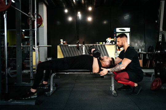 personal trainer helping and assisting man in the gym