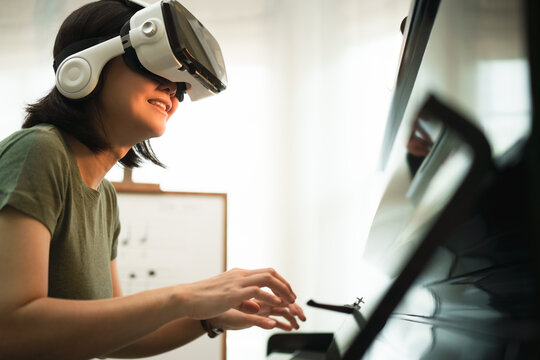 Young Asian woman have fun with new technology VR headset by playing piano music lesson at home, virtual reality musical online learning conceptual, Pianist conduct student from VR technology.