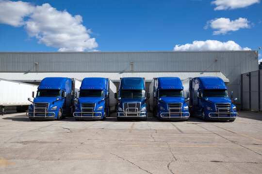 Blue Transport Trucks Lined Up in the Yard of a Warehouse