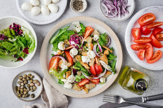 Healthy salad with tomatoes, croutons, greens and mozzarella cheese on a plate. Italian style Panzanella salad with mini mozzarella balls and capers