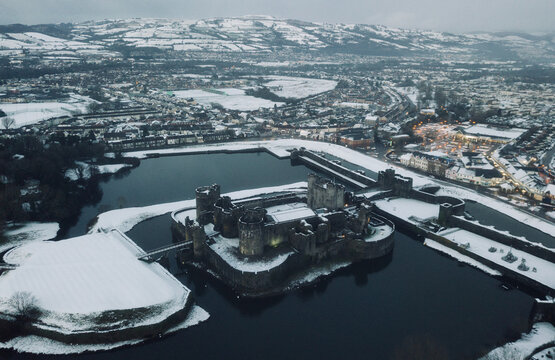 An aerial shot of Caerphilly Castle surround by snow.