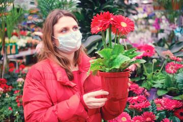 Adult woman florist in medical mask chooses gerbera flowers in shop. Home gardening hobby during corona virus quarantine Fototapete