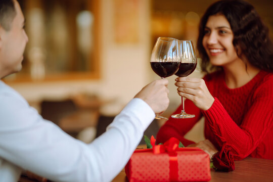 Clinking glasses with red wine. Romantic dinner. Valentines day, romantic date and holidays concept.