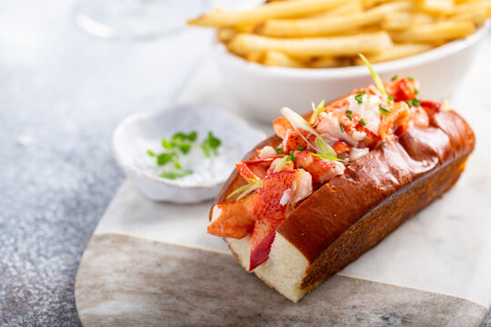 Lobster roll on a brioshe bun with fries on a marble board