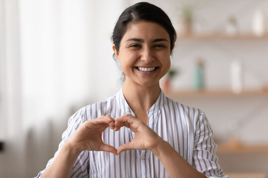 Portrait of happy smiling young lady of indian ethnicity looking at camera holding fingers joined in tender heart close to chest. Young woman volunteer video blogger ask audience to support charities
