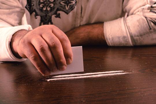 drug use, a person inhales cocaine and smokes marijuana.