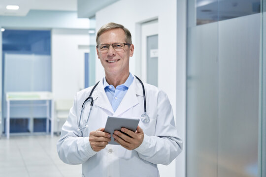 Smiling old middle aged doctor holding using digital tablet standing in hospital looking at camera. Online healthcare telemedicine ehealth services,medical internet technology apps,telehealth concept.