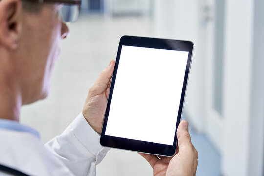 Male doctor holding digital tablet in hands using blank white mockup screen technology for medical healthcare tech website ads concept, video call e telehealth online appointment. Over shoulder view