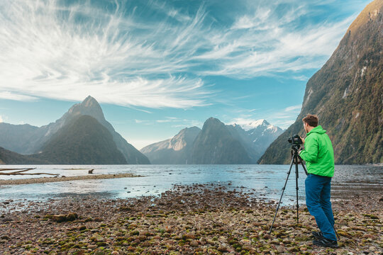 Tourist travel photographer taking pictures with professional camera on tripod on adventure travel vacation in mountain landscape. Milford Sound, Fiordland National Park, South Island, New Zealand.