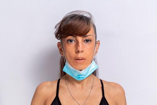 mulher mostrando o usa de incorreto da máscara protetora contra covid-19, ela está usando a mascar no queixo