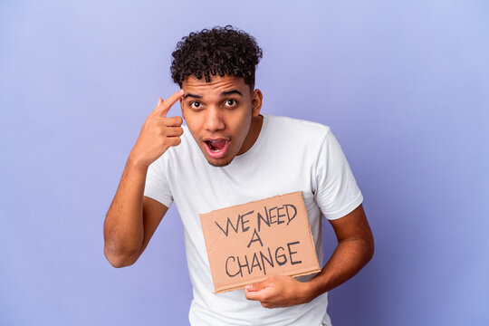 Young african american curly man isolated holding a we need a change cardboard showing a disappointment gesture with forefinger.