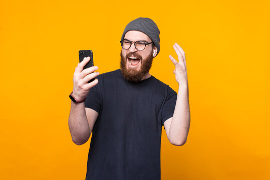 Photo of bearded hipster man looking angry at smartphone.