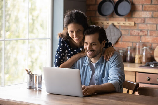 Smiling young Caucasian couple sit at table at home kitchen use laptop browsing wireless internet on gadget. Happy millennial man and woman look at computer screen shop online on device together.