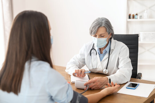 Senior mature female doctor wearing a lab coat and a face mask, using a blood pressure machine or sphygmomanometer with stethoscope to check a sick patient in the hospital during a pandemic