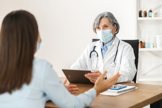 Senior middle-aged female doctor in a lab coat and a face mask sitting at the desk, holding a touchpad, discussing medical results with patient, young lady unhappy to hear that covid test is positive