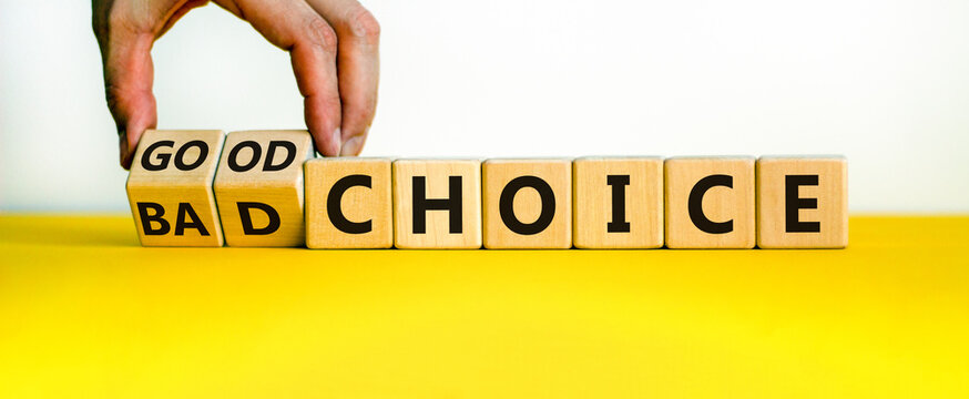 Good or bad choice symbol. Businessman turns wooden cubes and changes words 'bad choice' to 'good choice'. Beautiful yellow table, white background, copy space. Business and good choice concept.