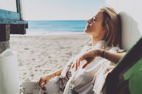Side view portrait of a blonde Caucasian woman with closed eyes wearing white shirt standing leaning to the wooden wall of a beach house while enjoying the sun warmth on a blurred sea side background.