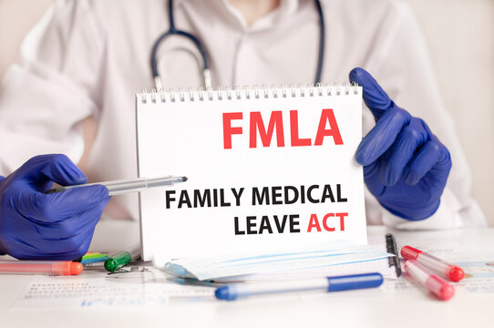 Doctor holding a tablet with text: FMLA. FMLA - Family Medical Leave Act, medical concept.