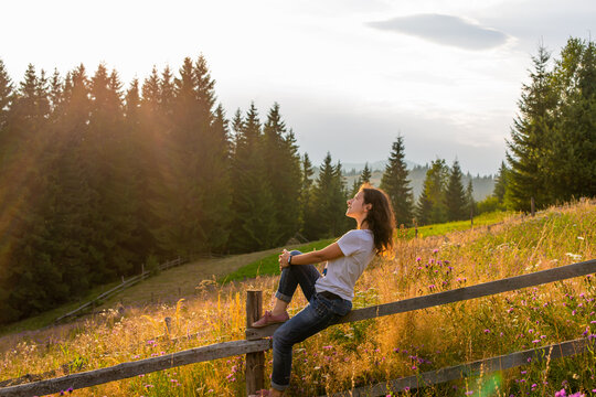The girl enjoy sunset sitting on wooden fence on highlands field next to forest